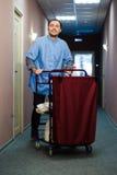 Il giovane che spinge un carretto del governo della casa caricato con gli asciugamani puliti, la lavanderia e le attrezzature per Immagine Stock