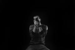 Il giovane che sta su una sedia e che guarda allinea una vecchia macchina fotografica sopra Fotografia Stock Libera da Diritti
