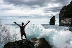 Il giovane che sta sulla roccia con il mare ondeggia irrompendo il frront Fotografia Stock
