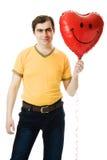 Il giovane che tiene un cuore rosso ha modellato l'aerostato Fotografie Stock Libere da Diritti