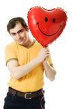 Il giovane che tiene un cuore rosso ha modellato l'aerostato Immagini Stock Libere da Diritti