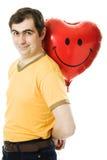 Il giovane che tiene un cuore rosso ha modellato l'aerostato Fotografia Stock Libera da Diritti