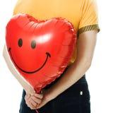 Il giovane che tiene un cuore rosso ha modellato l'aerostato Fotografia Stock