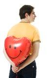 Il giovane che tiene un cuore rosso ha modellato l'aerostato Immagine Stock