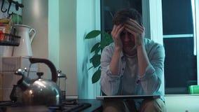 Il giovane chiude il computer che si siede alla cucina mentre bollitore che bolle sulla stufa stock footage