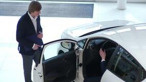 Il giovane cliente ispeziona un'automobile nel concessionario auto archivi video