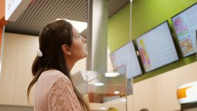 Il giovane compratore attraente della ragazza sceglie il menu in caffè archivi video