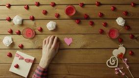 Il giovane con i cuori fatti a mano di carta si siede dalla tavola, vista superiore archivi video