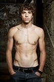Il giovane con i muscoli addominali sta levandosi in piedi Fotografia Stock