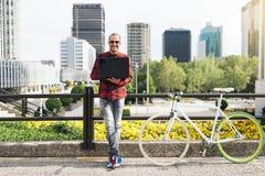 Il giovane con il computer portatile e l'ingranaggio fisso vanno in bicicletta nella città Fotografia Stock