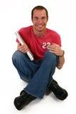 Il giovane con il computer portatile si siede sul pavimento Fotografia Stock Libera da Diritti