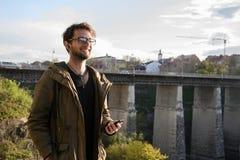 Il giovane con il supporto del telefono cellulare, fondo è ponte e vecchia città Fotografia Stock Libera da Diritti