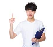 Il giovane con la lavagna per appunti ed il dito indicano su Immagini Stock Libere da Diritti