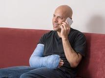 Il giovane con un braccio ha fuso la conversazione sul suo telefono Fotografie Stock