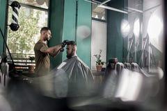 Il giovane con una barba si siede nella sedia ad un negozio di barbiere Il barbiere asciuga i capelli degli uomini fotografie stock libere da diritti