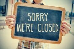 Il giovane con una lavagna con il testo spiacente siamo chiusi, f Fotografia Stock Libera da Diritti