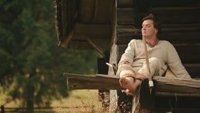 Il giovane connazionale carpatico nel ukrainain tradizionale copre la seduta sul punto del riparo della montagna di Carpathians stock footage