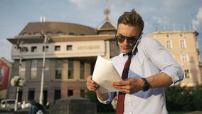 Il giovane controlla le sue carte che stanno sulla via archivi video