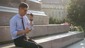 Il giovane controlla il suo telefono che sta sulla via video d archivio