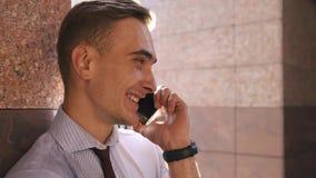 Il giovane controlla il suo telefono che sta sulla via stock footage