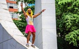 Il giovane in corona rosa, la parrucca gialla, il body con l'ananas ed il tutu rosa luminoso fiancheggiano la condizione al Varga Fotografie Stock Libere da Diritti