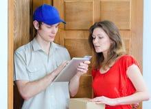 Il giovane corriere consegna il pacchetto Immagini Stock