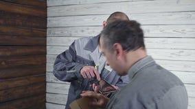 Il giovane corriere in un'uniforme grigia ha portato un pacchetto al cliente video d archivio