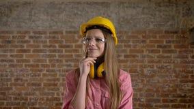 Il giovane costruttore butiful della ragazza ottiene l'idea, il processo di pensiero, fondo del mattone archivi video