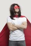 Il giovane in costume dell'eroe eccellente che sta con le armi ha attraversato contro fondo grigio Immagine Stock Libera da Diritti