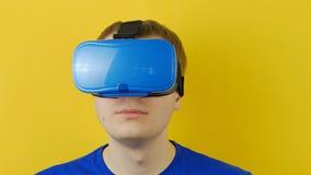 Il giovane in cuffia avricolare del vr guarda intorno, realtà virtuale, esposizione testa-montata video d archivio