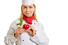 Il giovane cuoco tiene il cuore ed il basilico fotografie stock libere da diritti