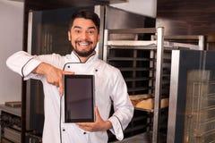 Il giovane cuoco unico allegro sta mostrando l'attrezzatura moderna Fotografie Stock
