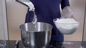 Il giovane cuoco unico versa la farina nella ciotola in cucina del ristorante video d archivio