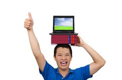 Il giovane dà i suoi pollici in su con il libro ed il computer portatile Immagini Stock
