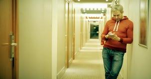 Il giovane dai capelli grigio in abbigliamento casual utilizza il suo smartphone nel corridoio dell'hotel video d archivio