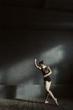 Il giovane dancing della ginnasta nello scuro ha acceso la stanza Fotografie Stock