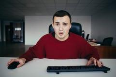 Il giovane dei pantaloni a vita bassa che lavora nell'ufficio imbarazzato esamina il monitor del vostro computer In camera vista  fotografie stock