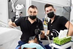 Il giovane dentista e suo l'assistente che mostrano il dito gesture la classe fotografia stock