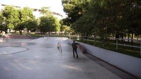 Il giovane di Determinated che corre sui pattini di rullo in-linea alla rampa nel parco pubblico del pattino, fa un salto ed appe video d archivio