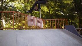 Il giovane di Determinated che corre sui pattini di rullo in-linea alla rampa nel parco pubblico del pattino, fa un salto ed appe stock footage