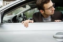 Il giovane di Dissapointed sta dando una occhiata a dalla finestra Sta esaminando qualcosa dietro la sua automobile fotografia stock