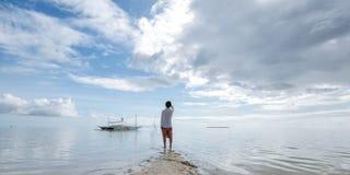 Il giovane diritto esamina l'orizzonte sulla spiaggia fotografie stock