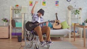 Il giovane disabile in una sedia a rotelle nel musicista di vetro di realtà virtuale gioca la chitarra elettrica stock footage