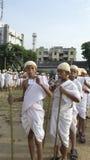 Il giovane distintivo della tenuta del ragazzo si è vestito su come Mahatma Gandhi per il mondo r Immagine Stock