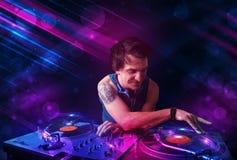 Il giovane DJ che gioca sulle piattaforme girevoli con gli effetti della luce di colore Immagine Stock