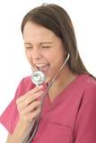Il giovane dottore femminile attraente Screaming Down uno stetoscopio Fotografie Stock