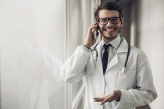 Il giovane dottore sorridente Talking sul telefono in ufficio fotografie stock libere da diritti