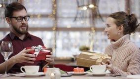 Il giovane e la donna stanno scambiando i regali in retaurant e la donna sta guardando dentro la sua scatola attuale video d archivio