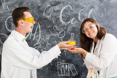 Il giovane e la donna in un laboratorio di chimica hanno creato un elisir immagini stock