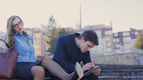 Il giovane e signora di affari stanno sedendo su un banco nel parco archivi video